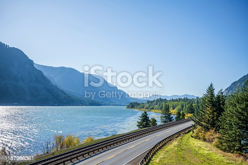 A railroad track next to a highway road with lane dividing opposite traffic runs along the scenic Columbia River bank with green trees and rocky mountains in Columbia Gorge area