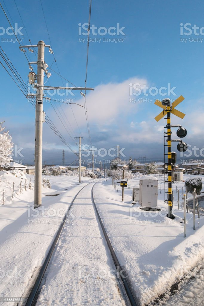 Railway track for local train with white snow fall in Japan royalty-free stock photo