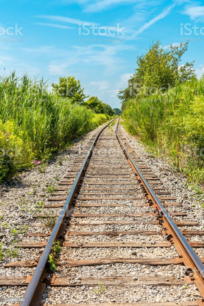 Scenic view of an abandoned railroad line, under a summer blue sky,...