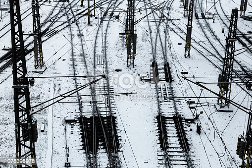 Color image depicting many railroad tracks diverging in the snow as they make their way towards their various travel destinations. Room for copy space.