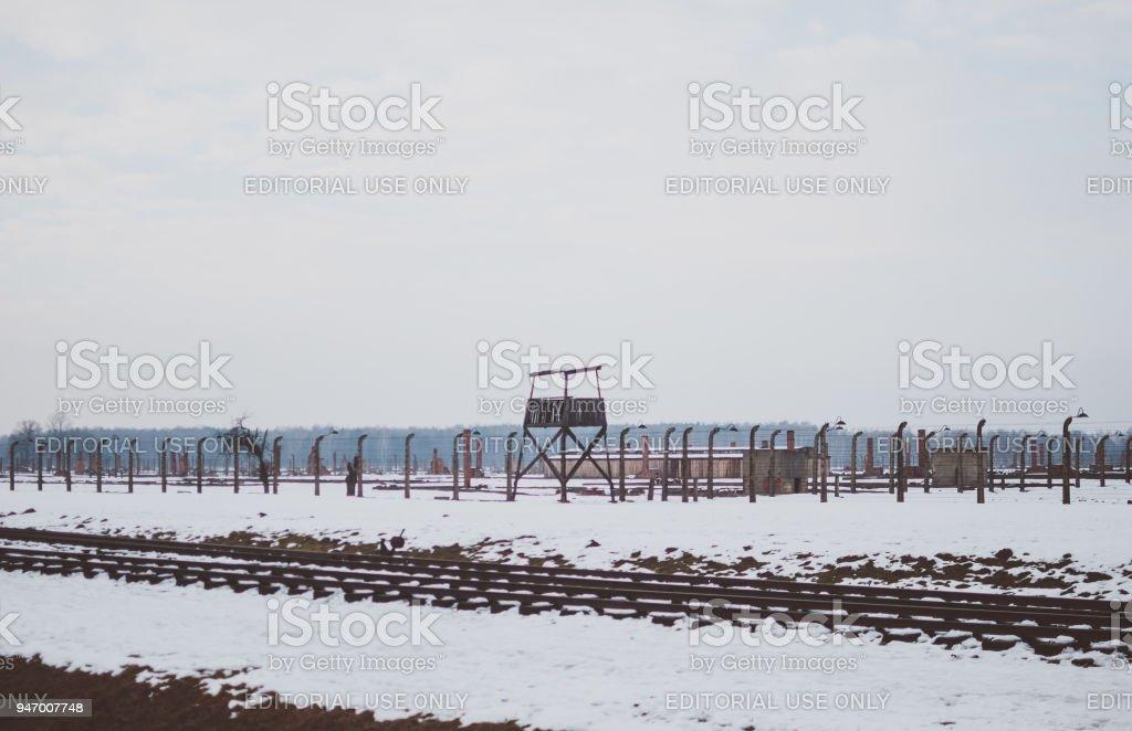 Gleisanlagen des KZ Auschwitz-Birkenau und einem Wachturm. – Foto