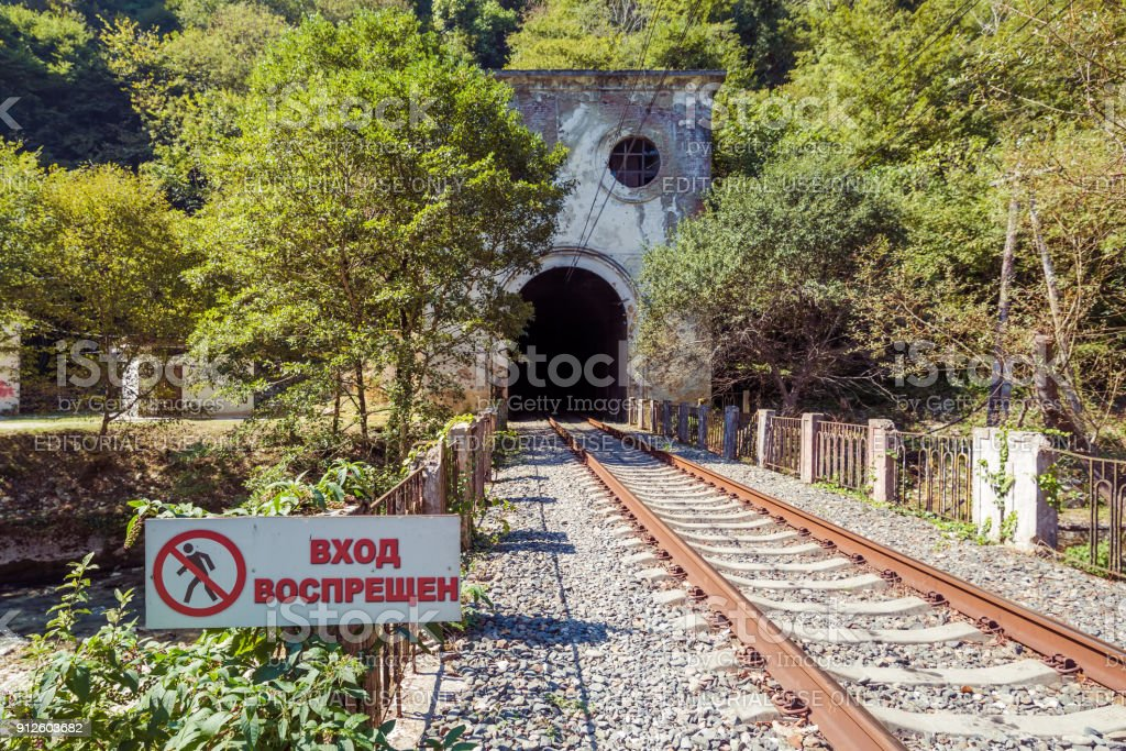 Railway tunnel in the mountain and the sign Â«No entrance' near the Psirtskha Railway Station stock photo