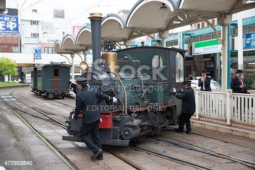 Matsuyama, Japan - April 13, 2015: Train conductors turning the Botchan Ressha steam locomotive train on a turntable at the Matsuyama City Station in Ehime Prefecture, Shikoku, Japan.