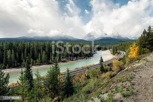 Railway with rocky mountains and cloudy in autumn valley at Morant's Curve, Calgary, Canada