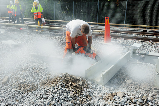 Stockholm, Sweden - August 14, 2011: Railway worker, cutting concrete. More workers in safety vests in background.