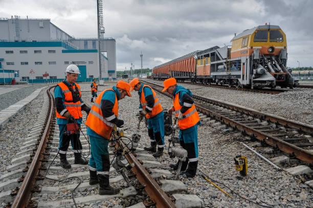 cheminots réparation ferroviaire sous la pluie - transport ferroviaire photos et images de collection