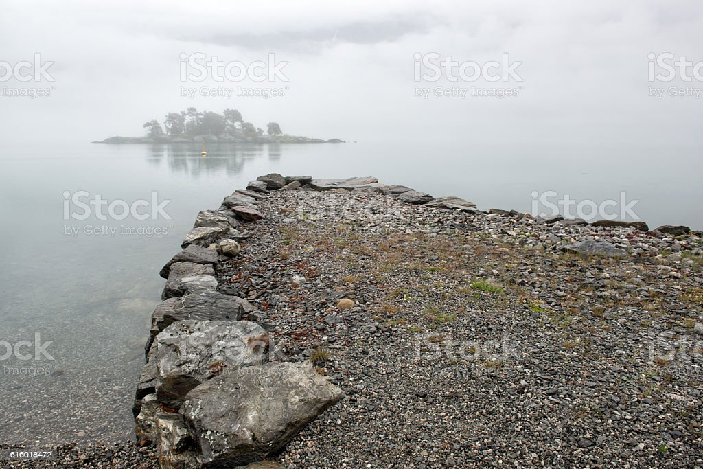 Rain and fog on fjord, island in the mist, Norway stock photo