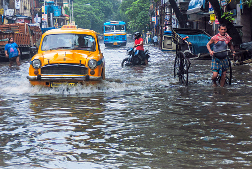 After the rain the road is flooded with water, between its a yellow taxi and a hand pulled risk is passed at Kolkata, India.