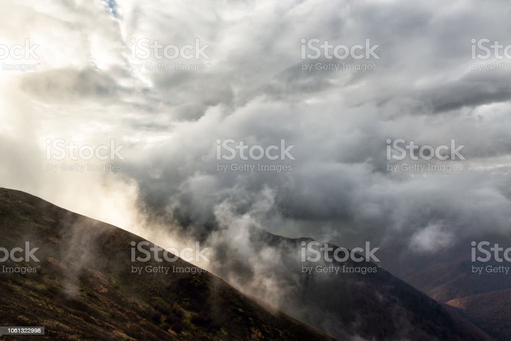 Rain clouds on the mountain hills. Dramatic landscape with bad weather