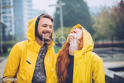 Couple having fun at rain. Wearing raincoats and enjoying in their love. It's raining night and they walk through city