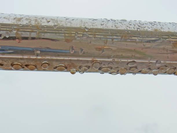 フェンスから滴り落ちる雨。 ストックフォト