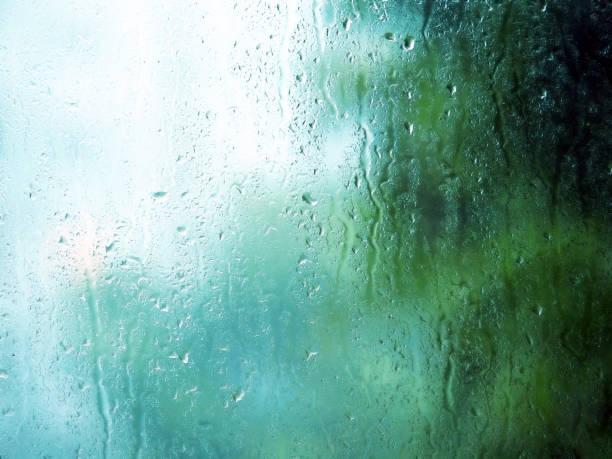 regen druppels en water vlekken op glas in regenachtige zomerdag. - luchtvochtigheid stockfoto's en -beelden