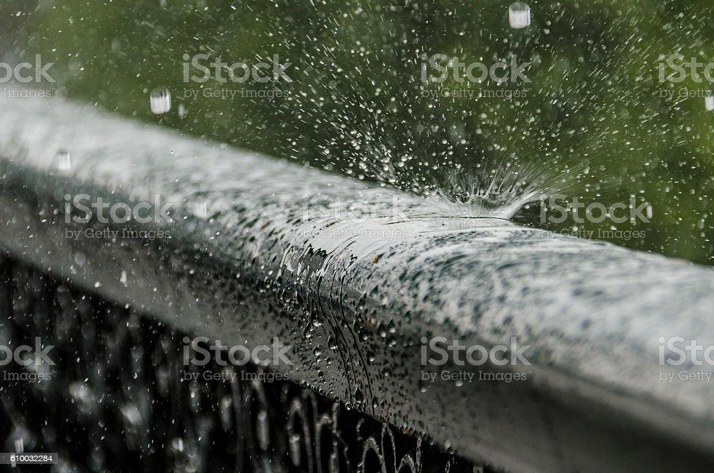 Rain drops bouncing off metal railing stock photo