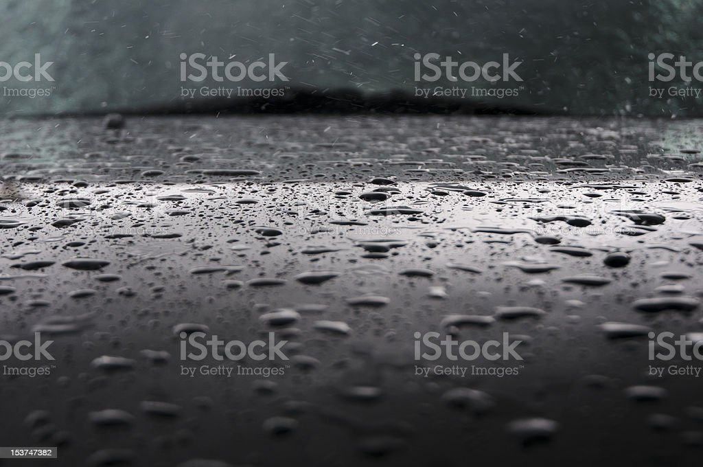 rain drops fall on black car bonnet stock photo