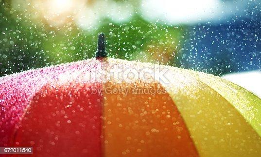 istock Rain drops falling onto umbella with rainbow colour 672011540