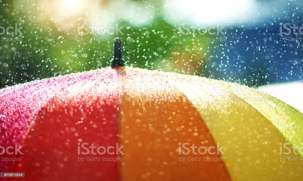 Rain drops falling onto umbella with rainbow colour stock photo