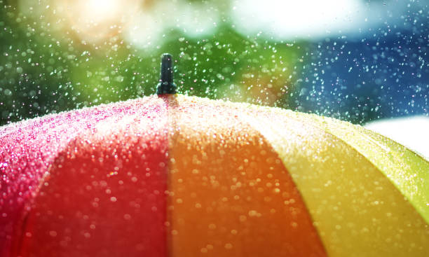 rain drops falling onto umbella with rainbow colour - fall prevention stock photos and pictures