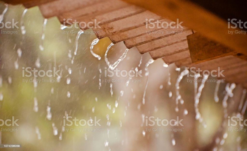 Rain drops of water falling from a tin shed rooftop stock photo