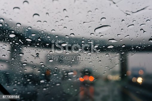 1054750504 istock photo Rain drops on a car window - Road view through car window 877309164