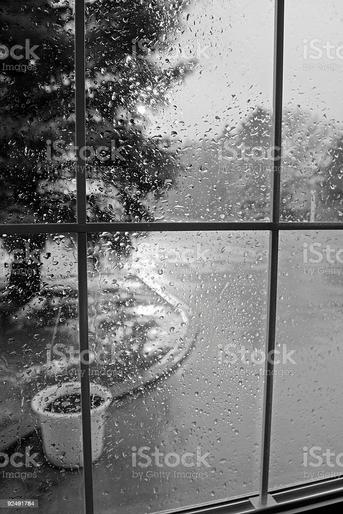 Rain drops on a window with view outside in black and white royalty-free stock photo