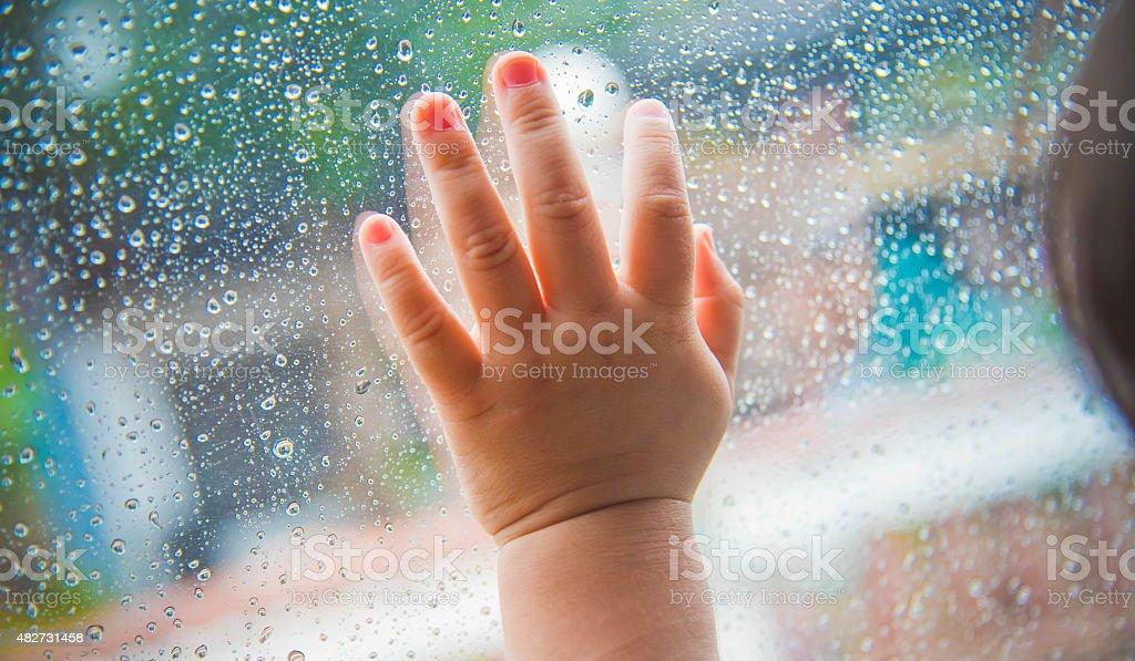 Rain drops on the car window and children hand . stock photo