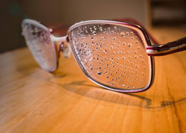 Regenfällt auf die Linse einer Brille auf einem Holztisch, mit leichtem Linsenflackern. – Foto