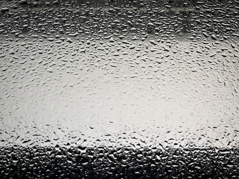 Rain drops on the window glass in the city.