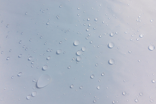 Rain drops on waterproof canvas after the storm. Softened photo.