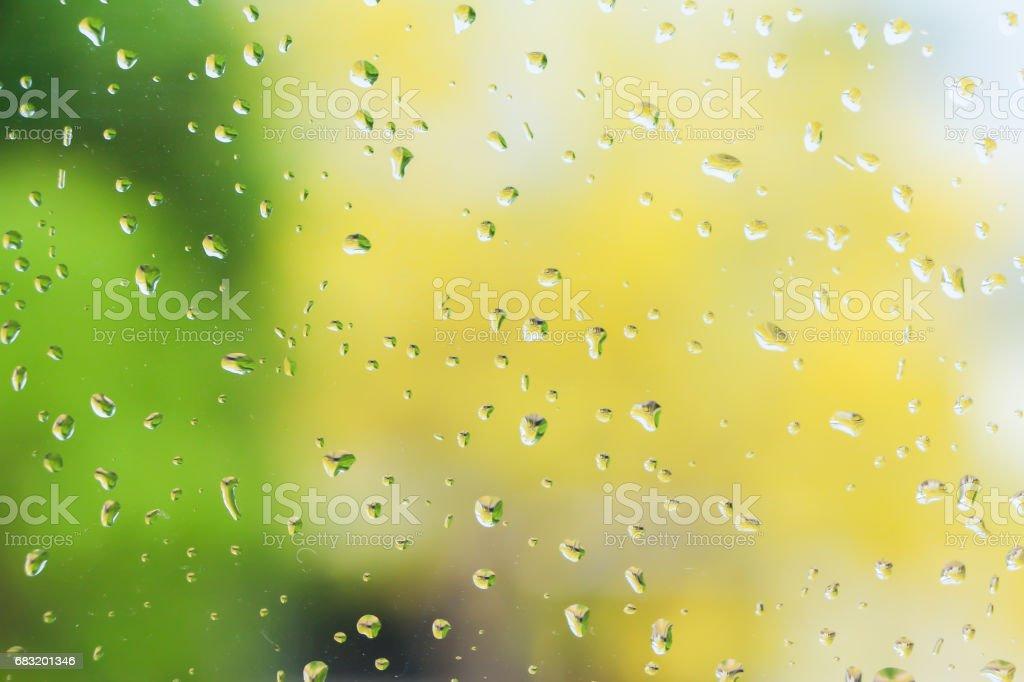 Rain drops on glass window blurry background