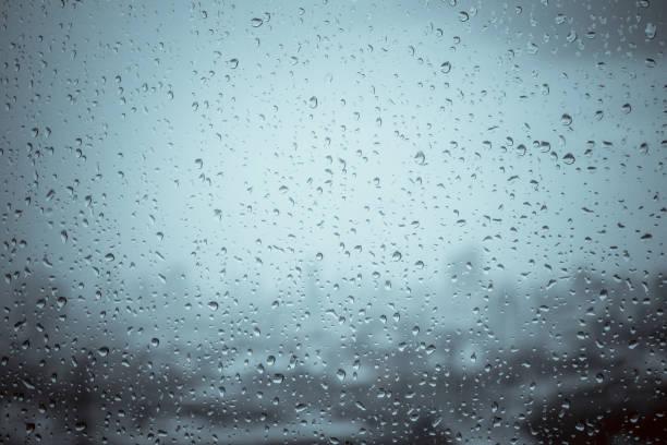 krople deszczu na szybie okna na zewnątrz tekstury tle wody wspaniały ulewny deszczowy dzień z chmurami nieba w mieście niebieski zielony rozmyte światła abstrakcyjne słońce cieszyć się relaksującą tapetę przyrody - deszcz zdjęcia i obrazy z banku zdjęć