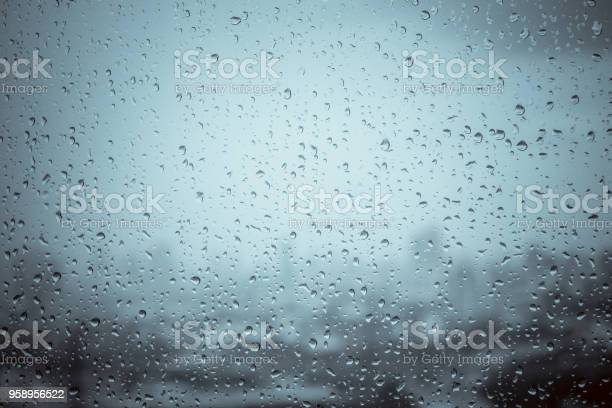 Photo of Rain drops on window glass outside texture background water of wonderful heavy rainy day with sky clouds at city blue green blurred lights abstract view sunshine enjoy the relaxing nature wallpaper