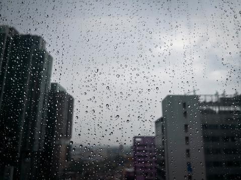 Rain drops on window glass with blurred skyscraper building in the city.