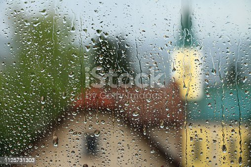 istock Rain drops on window glass with house and church in background 1125731303