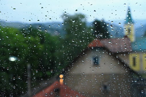 istock Rain drops on window glass with house and church in background 897011888