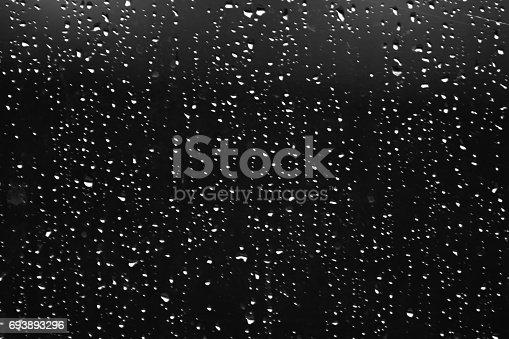 Rain drops on the window glass in a night.