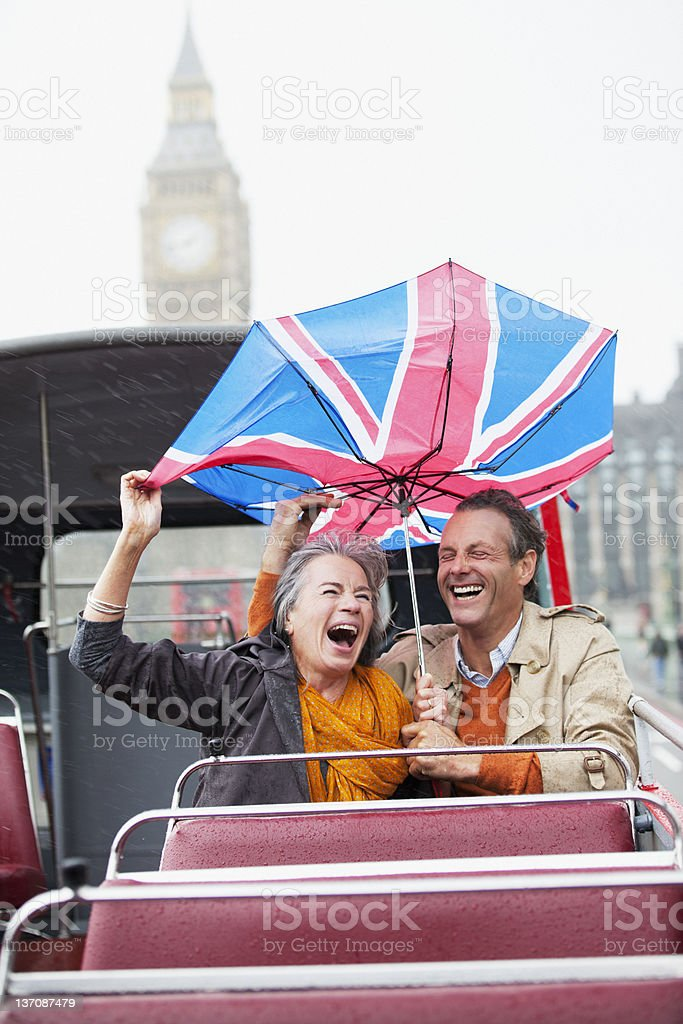 Rain falling on couple with British Flag umbrella on double decker bus stock photo