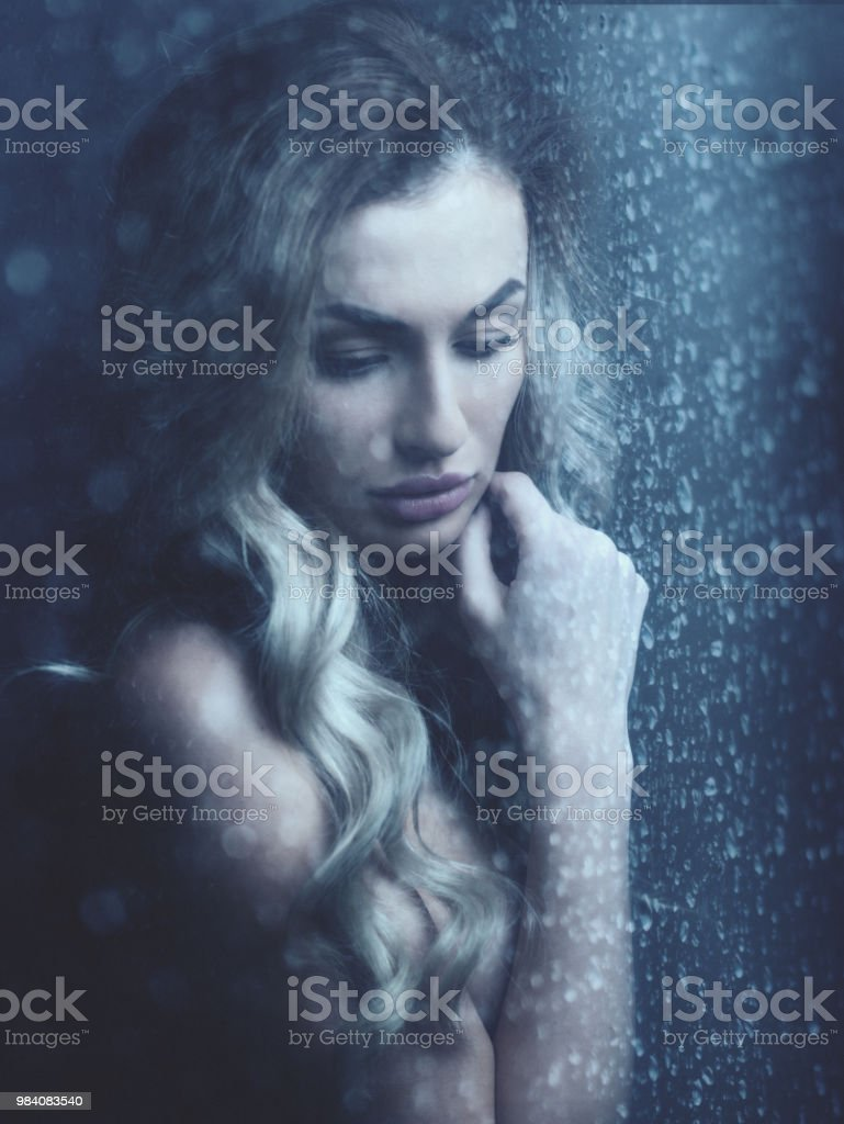 Rain. Female portrait, beauty young woman behind the window with...