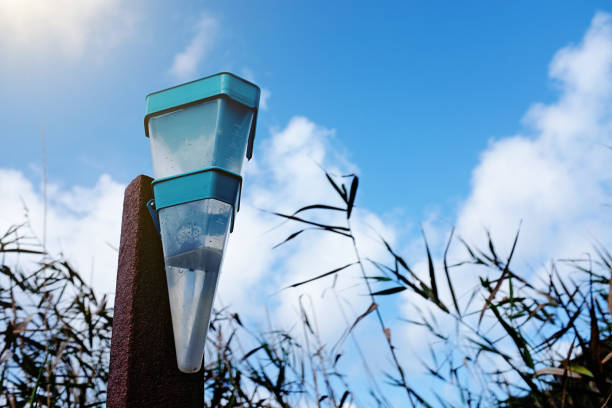 rain gauge against lightly clouded sky - rain gauge stock photos and pictures