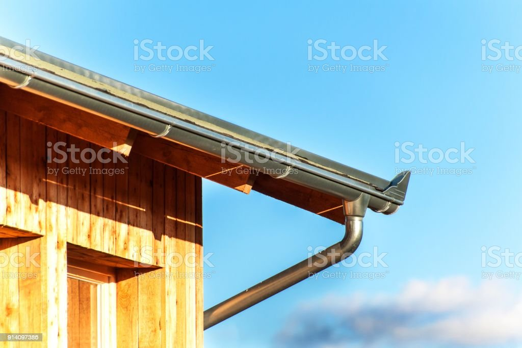 Rain gutter on the roof ecological house. Zinc gutter on the woodwork. stock photo