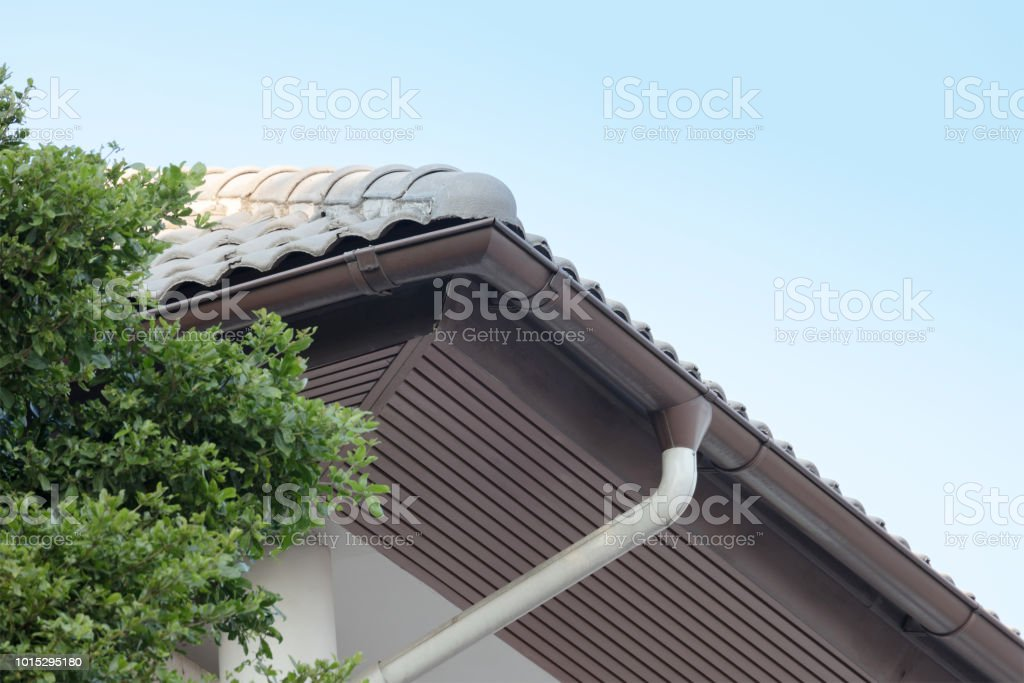 rain gutter on top of roof against blue sky on background