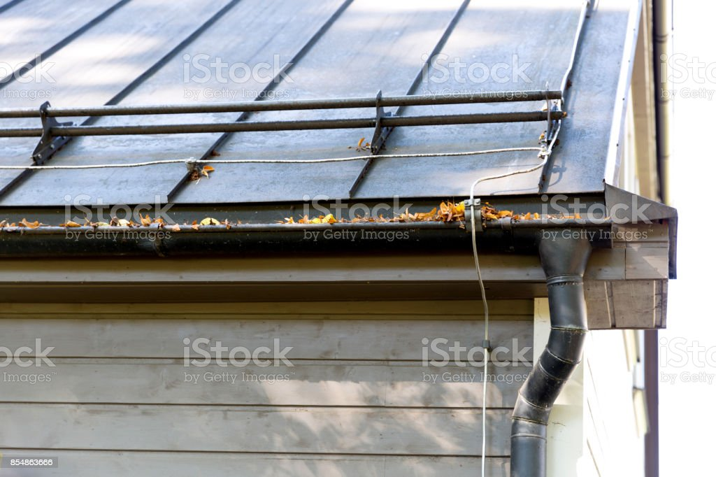 Rain gutter pipeline system installation. Roofing construction. Rain gutter system and roof protection from snow (Snow guard) stock photo