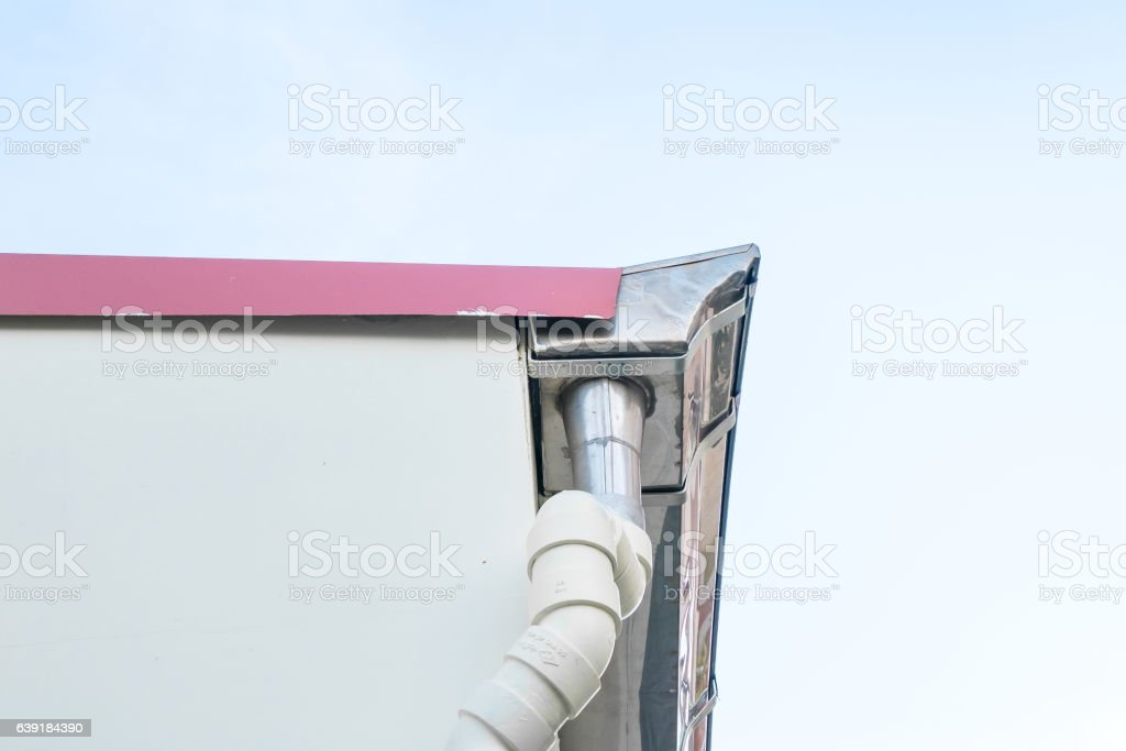 Rain gutter system on roof of House against Blue Sky stock photo