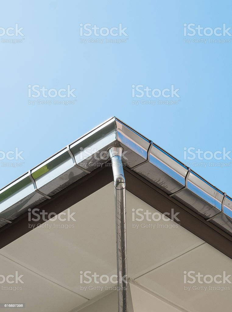 Rain gutter system on roof of House against Blue Sky - Can use for...