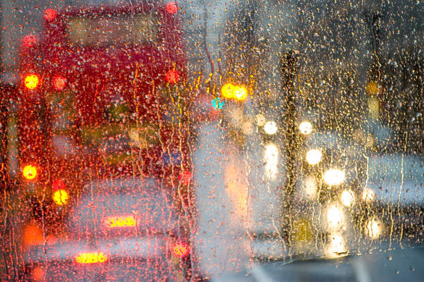 Rain in London view to red bus through rain-specked window stock photo