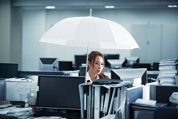 Rain in Office Woman holding an umbrella while working in office excessive obsession stock pictures, royalty-free photos & images