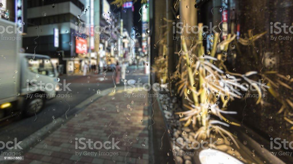 Rain in Tokyo, Japan through a glass window effect stock photo