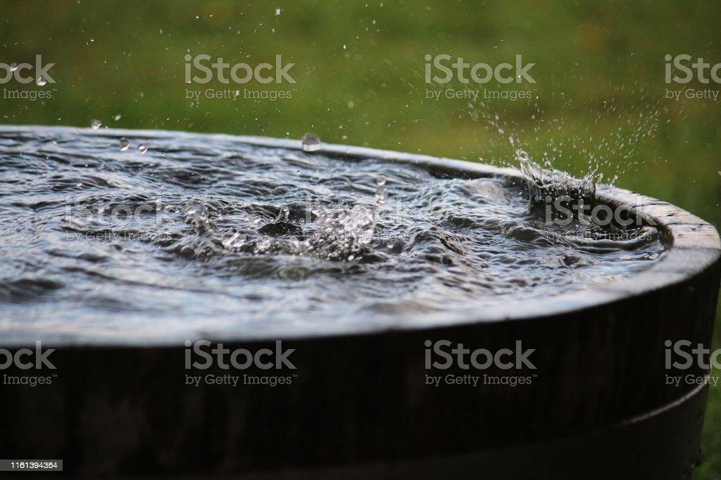 lluvia está cayendo en un barril de madera lleno de agua en el jardín - Foto de stock de Abstracto libre de derechos