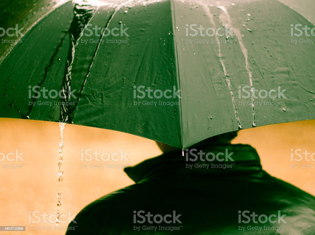 Close-up shot of man with a black umbrella, with water streaming off,...