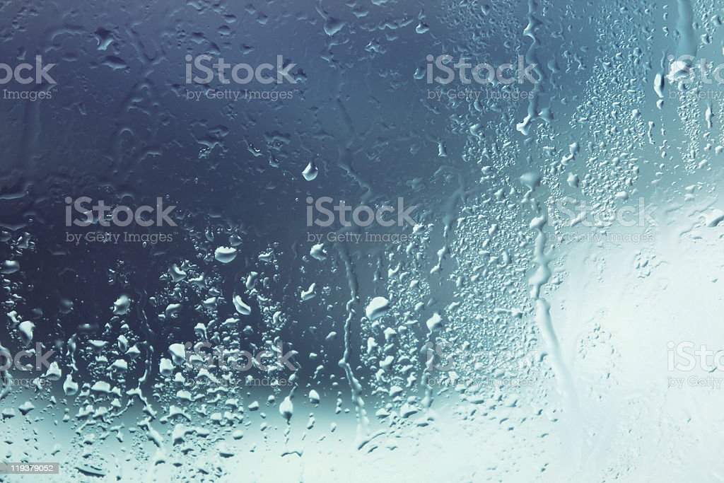 Rain on a window with a blue background royalty-free stock photo