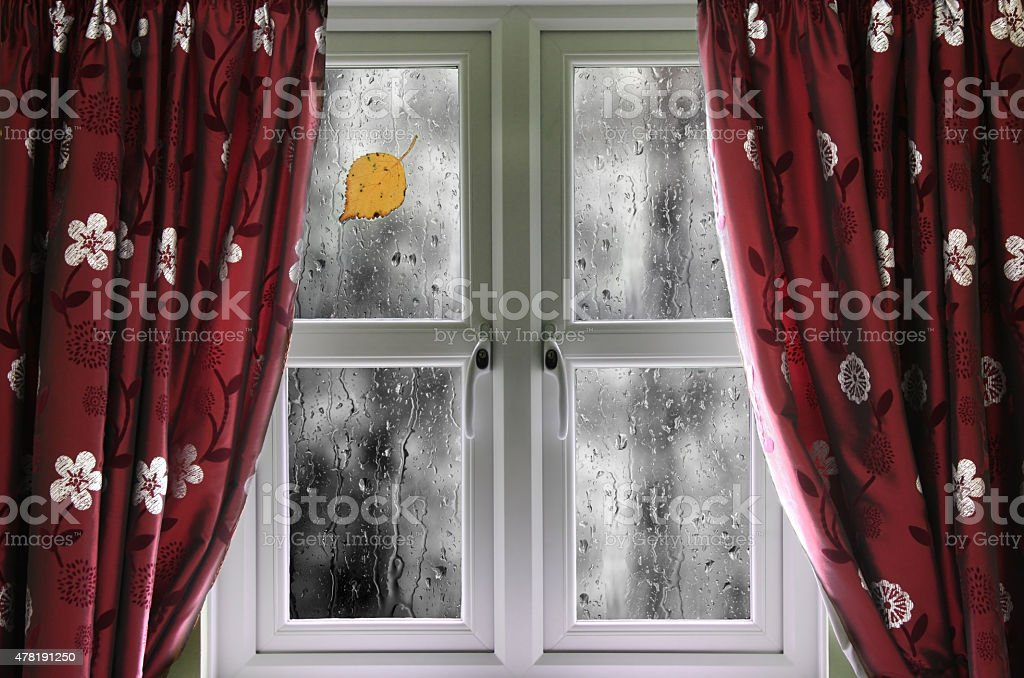 Rain on a window with curtains stock photo